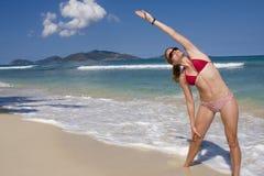 Estiramentos de uma mulher nova na praia fotos de stock