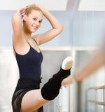 Estiramentos ela mesma do dançarino de bailado perto da barra imagem de stock royalty free