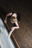 Estiramentos fêmeas do dançarino de bailado Imagem de Stock