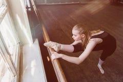Estiramentos fêmeas do dançarino de bailado Imagens de Stock