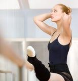 Estiramentos fêmeas ela mesma do dançarino de bailado perto da barra fotografia de stock
