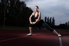 Estiramiento de la aptitud del atleta de la mujer en pista del atletismo foto de archivo