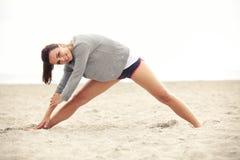 Estiramientos que hacen femeninos sonrientes en la playa fotos de archivo