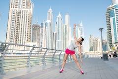 Estirando y entrenamiento de los deportes Mujer atlética en doi de la ropa de deportes Fotografía de archivo