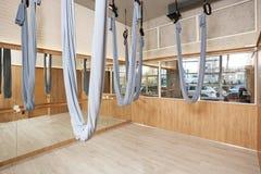 Estirar el interior del estudio con las hamacas de seda y los espejos de la yoga aérea foto de archivo libre de regalías