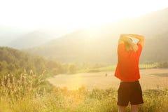 Estirar entrenamiento del ejercicio durante puesta del sol Fotografía de archivo