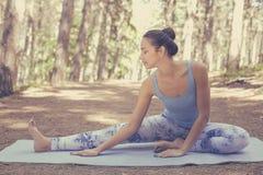 Estirar a la mujer en yoga que hace feliz sonriente del ejercicio al aire libre imagenes de archivo