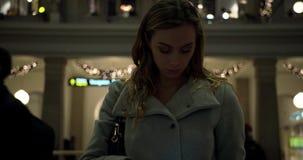 ESTOCOLMO, SUECIA - 26 DE NOVIEMBRE DE 2018 - mujer joven que comprueba salidas del teléfono y del tren en la estación central almacen de metraje de vídeo