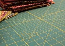 Estofe a esteira giratória do corte com tela colorido no fundo Imagens de Stock