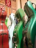 Estojos multicoloridos coloridos do violoncelo que estão na exposição Foto de Stock