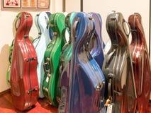 Estojos multicoloridos coloridos do violoncelo que estão na exposição Imagens de Stock