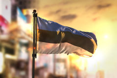 Estonia Flag Against City Blurred Background At Sunrise Backligh. T Sky Royalty Free Stock Photos