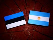 Estonia flag with Argentinian flag on a tree stump isolated Stock Photos