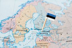 Estonia flag pin on map. Paper flag pin of Estonia on a world map showing neighboring countries royalty free stock photo