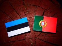 Estonia flag with Portuguese flag on a tree stump isolated. Estonia flag with Portuguese flag on a tree stump royalty free illustration