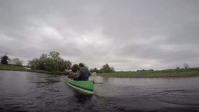 Estonia, May 2015, US Soldiers River Trip With. US soldiers paddles in a small boat with children along a river stock footage