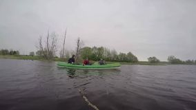 Estonia, May 2015, US Soldiers River Trip With. US soldiers paddles in a small boat with children along a river. At the riverside is a nice nature with trees stock footage
