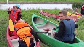 Estonia, May 2015, US Soldiers River Trip With. A US soldiers shows children how to use the paddle for a river trip stock video