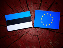 Estonian flag with EU flag on a tree stump isolated. Estonian flag with EU flag on a tree stump Royalty Free Stock Image
