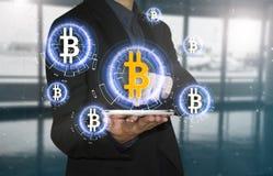 Estoque do bitcoin da oferta da imprensa da mão do negócio na tabuleta Fotos de Stock