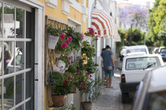 Estoril little street on summer time, colorful flowers in pots on the wall Stock Image