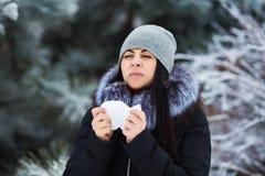 Estornudo femenino La mujer bastante joven tiene gripe y fiebre en el día de invierno al aire libre foto de archivo