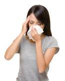Estornudo y dolor de cabeza asiáticos de la mujer Imagen de archivo