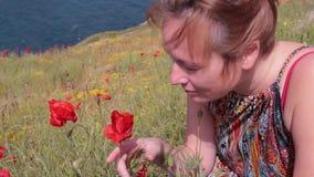 Estornudos de la muchacha porque ella está oliendo las flores Amapola alergia almacen de video