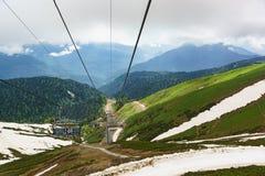 Estosadok, Sochi, Rusia - 10 de junio 2017: Los turistas suben la montaña en teleférico a la estación de esquí Imagenes de archivo