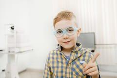 Estrabismos do menino da criança nos vidros para os olhos da vista, olhares no quadro fotografia de stock royalty free