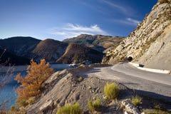 Estrada alpina ao longo da costa de um lago Imagem de Stock