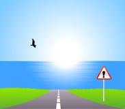 Estrada ao mar com sinal da atenção Imagens de Stock Royalty Free