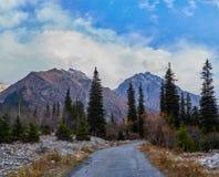 Estrada aos picos de montanha neve-tampados fotos de stock royalty free