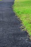 A estrada asfaltada é junto com a grama Imagem de Stock