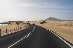 A estrada asfaltada através das dunas de areia Fotos de Stock
