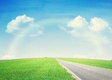 Estrada asfaltada através do campo e do arco-íris verdes Fotografia de Stock