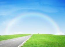 Estrada asfaltada através do campo e do arco-íris verdes Imagem de Stock