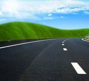Estrada asfaltada através do campo verde e nuvens no céu azul imagem de stock royalty free