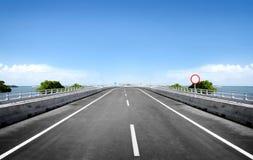 Estrada asfaltada através do mar Imagens de Stock Royalty Free