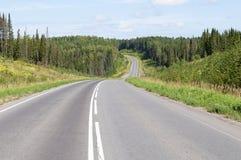 Estrada asfaltada através dos montes Imagens de Stock