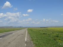 Estrada asfaltada através dos prados Fotografia de Stock Royalty Free