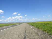 Estrada asfaltada através dos prados Imagens de Stock