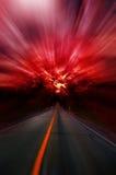 Estrada asfaltada borrada e céu borrado sangrento vermelho Imagens de Stock
