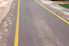 Estrada asfaltada com as duas linhas amarelas e marcas do passeio, brancas e foto de stock royalty free