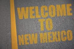 estrada asfaltada com boa vinda do texto a New mexico perto da linha amarela foto de stock