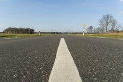 Estrada asfaltada com linha branca e o céu azul Imagem de Stock