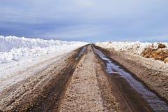 Estrada asfaltada com neve suja na mola adiantada imagens de stock