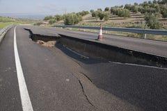Estrada asfaltada com uma quebra causada por corrimentos imagens de stock royalty free