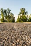 Estrada asfaltada entre a linha de árvore borrada Fotografia de Stock