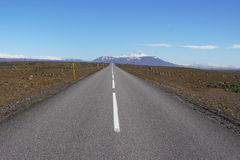 Estrada asfaltada longa F35 na Islândia central entre campos marrons e na frente das montanhas islandêsas altas Fotografia de Stock Royalty Free